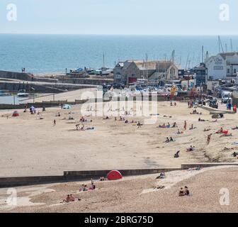 Lyme Regis, Dorset, Royaume-Uni. 21 mai 2020. Météo au Royaume-Uni: Les habitants et les familles apprécient le soleil chaud de l'après-midi à la station balnéaire de Lyme Regis. Malgré les parkings fermés, la plage était plus fréquentée cet après-midi, avec des personnes responsables qui maintenaient des distances sociales pendant qu'elles baignaient le soleil. Crédit : Celia McMahon/Alay Live News Banque D'Images