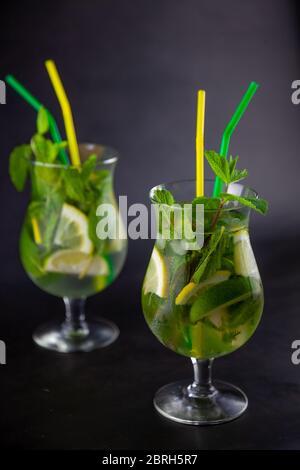 Cocktail mojito rafraîchissant à la menthe d'été avec rhum et glace sur fond noir. Cocktail Mojito sur une table en pierre sombre. Verre haut vitreux pour