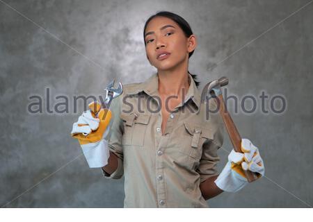 Portrait de la jeune fille attrayante clé de construction et marteau dans l'ensemble et des gants souriant sur fond de mur de béton Banque D'Images