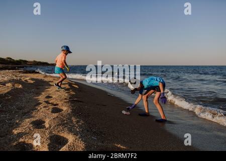Deux garçons nettoient les ordures sur la plage. frère de 5 et 10 ans portant des gants en caoutchouc pour ramasser la litière qui pollue la plage. Banque D'Images