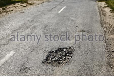 Route de très mauvaise qualité avec des nids-de-poule, réparation nécessaire Banque D'Images