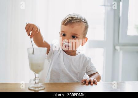 Charmant petit garçon concentré manger du yaourt en verre dans la cuisine lumineuse à la maison