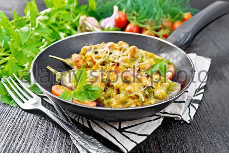 Aubergines farcies avec poitrine fumé, tomates, oignons, carottes à l'ail, le fromage et les herbes dans une casserole sur une serviette sur planche de bois contexte Banque D'Images