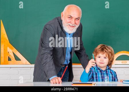 Portrait du grand-père et du fils en classe. Père et fils - concept de génération de personnes. Homme avec un vieux professeur apprenant en classe sur fond de couleur Banque D'Images