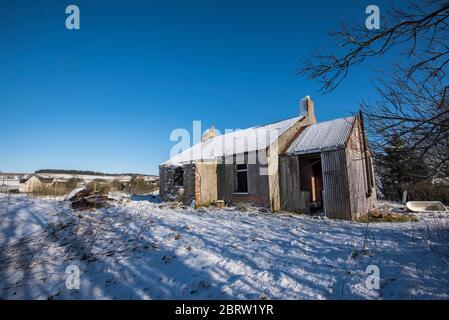 Maison abandonnée dans un cadre rural enneigé dans la campagne de Lamarkshire en Écosse. Banque D'Images