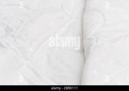 Couverture en tissu blanc avec mise au point sélective et flou d'arrière-plan. Motif petits carrés blancs. Banque D'Images