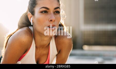 Photo d'une femme sportive portant des écouteurs, regardant loin et se concentrant sur son entraînement. Femme de sport se concentrant pendant l'entraînement, faites une pause en plein air