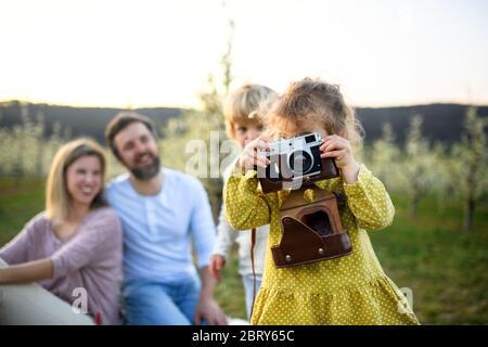Famille avec de petits enfants assis à l'extérieur dans la nature printanière, prendre des photos. Banque D'Images