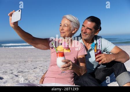 Couple caucasien senior prenant un selfie à la plage. Banque D'Images