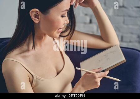 Jeune femme gaie à dessiner dans un carnet à la maison