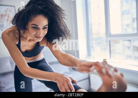 Femme souriante pratiquant le yoga à la maison