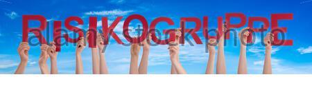 People Hands Holding Red German Word Risikogruppe signifie Groupe à haut risque. Ciel bleu comme arrière-plan Banque D'Images
