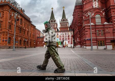 Moscou, Russie. 22 mai 2020 UN homme marche le long de la place Manège dans le centre de Moscou dans une combinaison de protection chimique pendant l'épidémie de coronavirus COVID-19 en Russie
