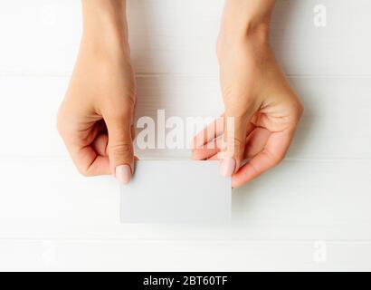 Femme tenant une carte de visite blanche entre les mains. Tamplate pour votre conception. Banque D'Images