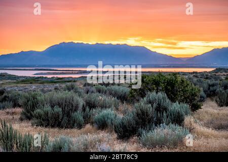 Lumière du soleil jaune-rouge-orange lever du soleil sur le Grand Lac salé dans le parc national d'Antelope Island Camping Ladyfinger avec réflexion sur l'eau et les rayons du soleil