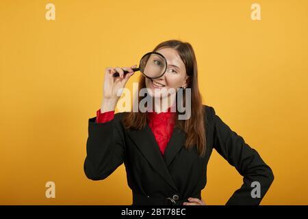 Femme souriante tient la loupe à la main et regarde avec l'œil. Scientifique
