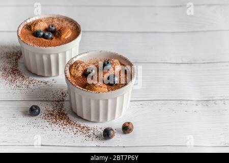 Délicieux dessert tiramisu avec biscuits au cacao et savoyardi dans des pots en céramique blanche avec copyspace sur fond gris Banque D'Images