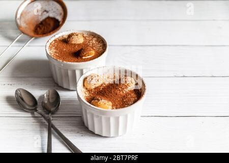 Délicieux dessert tiramisu avec biscuits au cacao et savoyardi dans des pots en céramique blanche sur fond gris Banque D'Images