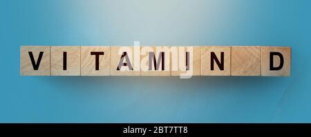 Mot de vitamine D fait de cubes en bois avec des lettres sur table bleu ciel. Concept de santé Banque D'Images