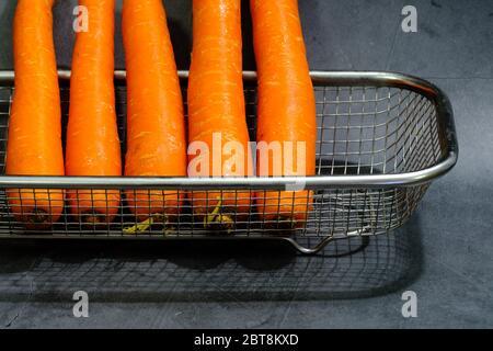 carotte fraîche dans un panier isolé sur fond noir Banque D'Images