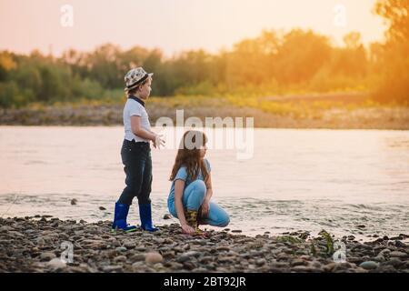 Un garçon blond en chapeau et une fille jouant sur la rive de la rivière. Les enfants pleurer les bottes en caoutchouc. Activités de printemps Banque D'Images