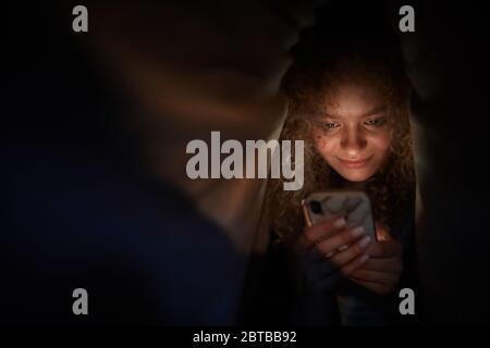 Portrait d'une jeune femme aux cheveux bouclés regardant l'écran du smartphone et souriant en étant allongé dans un lit dans une pièce sombre, espace de copie Banque D'Images