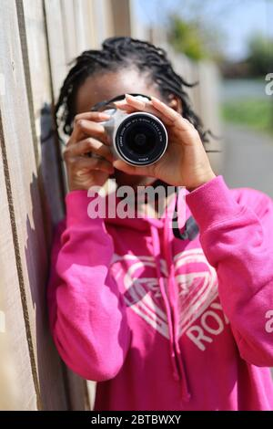 Une jeune fille noire avec des tresses pointant un appareil photo et prenant une photo tout en portant un sweat-shirt rose par temps ensoleillé