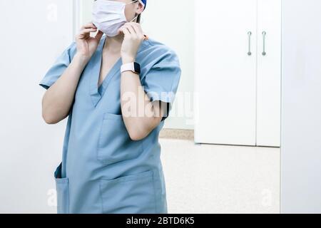 Une femme médecin se tient dans une pièce stérile lumineuse d'un hôpital et met un masque médical. Un médecin dans un uniforme médical bleu. Banque D'Images
