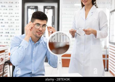 Spécialiste aidant un jeune homme à choisir des lunettes