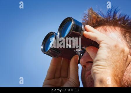 Homme de type extérieur regardant à travers des jumelles Banque D'Images