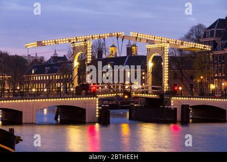 Amstel River Cityscape avec le célèbre pont skinny à Amsterdam, aux pays-Bas, tôt le matin en hiver