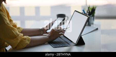 Photo d'une femme élégante tenant un smartphone et un stylet entre les mains tout en étant assise devant sa tablette d'ordinateur avec étui pour clavier qui met sur whit
