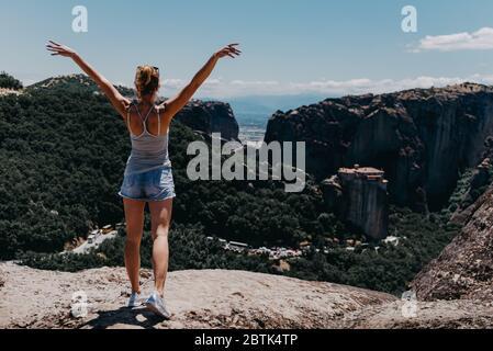 Jeune femme heureuse se tient à l'appareil photo avec les mains levées. Voyageur appréciant le paysage avec la montagne, monastères de Meteora, Grèce. Banque D'Images