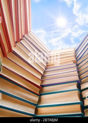 De grands livres pioche et ciel et soleil lumineux au-dessus. Thème de l'éducation, des sciences, de l'école et de l'étude