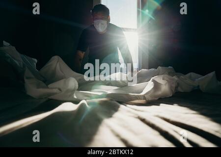 Homme asiatique nettoyant le lit le matin. L'action de la maison. La chambre est baignée de lumière. Banque D'Images