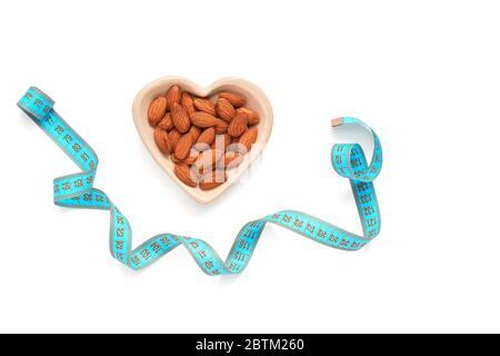 Amandes dans un bol en forme de coeur et ruban de mesure bleu isolé sur fond blanc. Le concept de perte de poids et de nourriture de régime. Vue de dessus, plan d'appartement