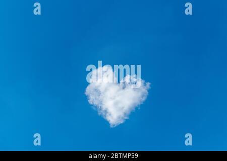 Nuage romantique en forme de coeur sur un ciel bleu. Concept d'amour. Banque D'Images