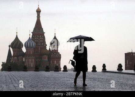 Moscou, Russie. 27 mai 2020. Une femme sous un parapluie marche sur la place Rouge dans le cadre de la pandémie COVID-19. Le régime d'auto-isolement en Russie est prolongé jusqu'au 31 mai afin d'empêcher la propagation du nouveau coronavirus. Credit: Mikhail Metzel/TASS/Alay Live News Banque D'Images