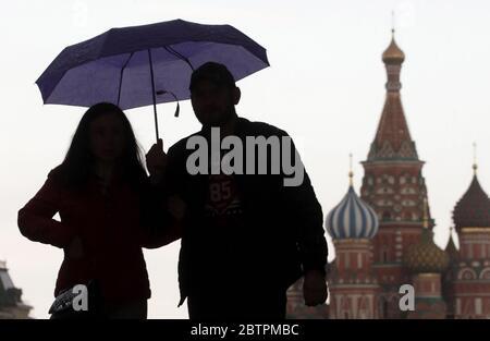 Moscou, Russie. 27 mai 2020. Des personnes sous un parapluie à pied dans la place Rouge dans le cadre de la pandémie COVID-19 en cours. Le régime d'auto-isolement en Russie est prolongé jusqu'au 31 mai afin d'empêcher la propagation du nouveau coronavirus. Credit: Mikhail Metzel/TASS/Alay Live News Banque D'Images