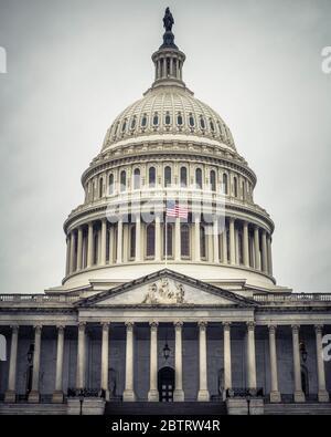 Le dôme de style néoclassique du bâtiment du Capitole des États-Unis contre un ciel gris et sombre à Washington, D.C.