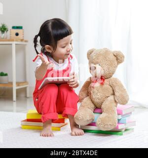 Adorable, riant petit enfant, petite fille d'âge préscolaire, portant un casque de sécurité jouant à l'intérieur de bâtiment maison avec des blocs colorés assis sur un sol Banque D'Images