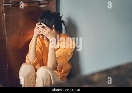 Une jeune femme contrariée assise sur le sol à la maison Banque D'Images