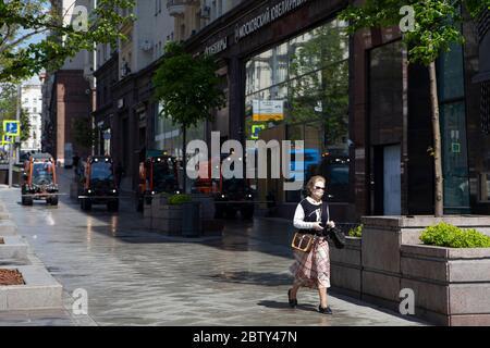 Moscou, Russie. 28 mai 2020. Une femme portant un masque se promène dans une rue alors que des véhicules de service public effectuent une désinfection dans le centre de Moscou, en Russie, le 28 mai 2020. La Russie a confirmé 8,371 nouveaux cas de COVID-19 au cours des 24 dernières heures, portant son nombre total d'infections à 379,051, a déclaré son centre de réponse au coronavirus jeudi. Credit: Alexander Zemlianichenko Jr/Xinhua/Alay Live News Banque D'Images