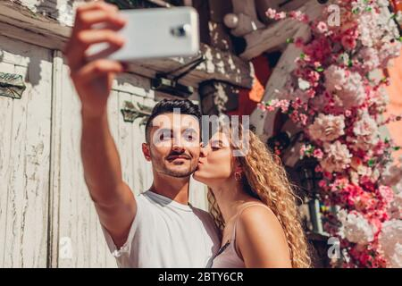 Couple de course mixte amoureux de prendre selfie sur smartphone marchant en ville. Bon homme arabe et femme blanche à ce jour Banque D'Images