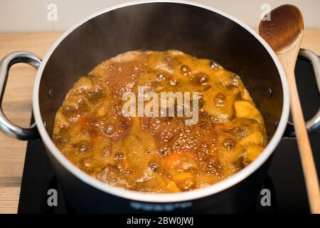 Préparation de la confiture d'abricot dans une casserole noire. Conserver les fruits bouillant dans une grande casserole avec une cuillère en bois. Banque D'Images