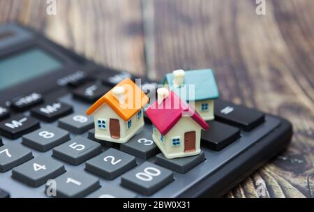 Acheter à la maison. La maison est placée sur la calculatrice. Planification d'économies argent de pièces pour acheter un concept de maison pour l'investissement immobilier, hypothécaire et immobilier.