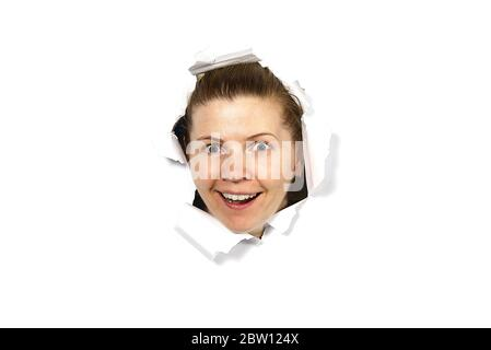 Une jeune femme qui pigne dans un trou sur papier. Femelle œil à travers trou. Isolé sur fond blanc. Concept espion Banque D'Images