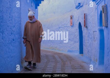Un marocain local en robe traditionnelle descend une ruelle étroite et pavée dans la vieille ville de Chefchaouen, Maroc.