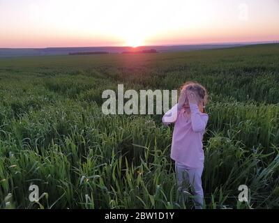 une petite fille avec ses yeux fermés dans un champ d'herbe verte au coucher du soleil