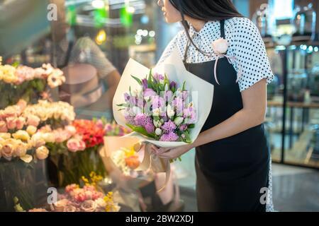 Brunette femelle en tablier tenant un bouquet de fleurs Banque D'Images